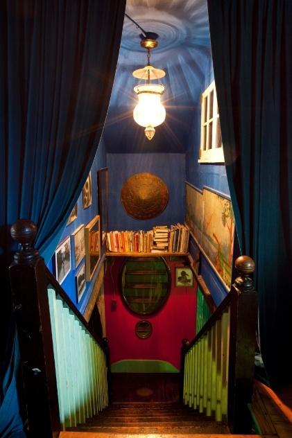 Cortinas pesadas, cores fortes, livros, quadros e um pendente indiano compõem a decoração da escadaria da casa dos artistas Jared Handelsman e Portia Munson, em Catskill (EUA)