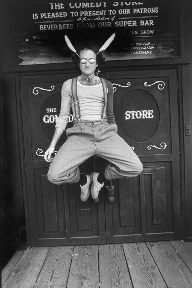 Sporting two horn-like feathers and bulbous white plastic eye-covers with pin-point holes to see through, Williams leaps kangaroo-style in the air in front of entrance to The Comedy Store nightclub in 1978.
