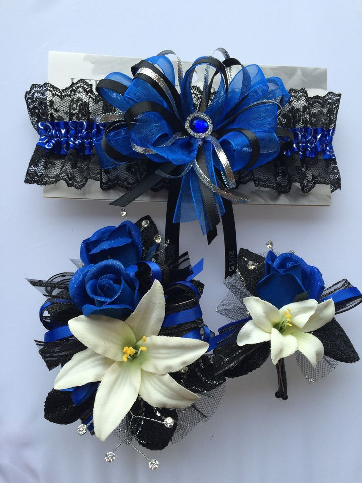 Royal blue silk roses with natural white lilies, rhinestone sprays, ribbon and black sparkle leaves with matching prom garter.  Garter prom corsage and boutonniere.  Lets Dance Garters