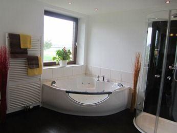 Das AKZENT Hotel Cordes bietete ein exklusives Badezimmer mit einem LCD-Fernseherausgerichtet zu dem Whirlpool und der Runddusche.