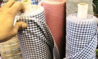 rolls of small black, green and blue checked fabirc