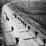 Soldati americani marciano al passo con le loro ombre verso Cassino a nord di Mignano