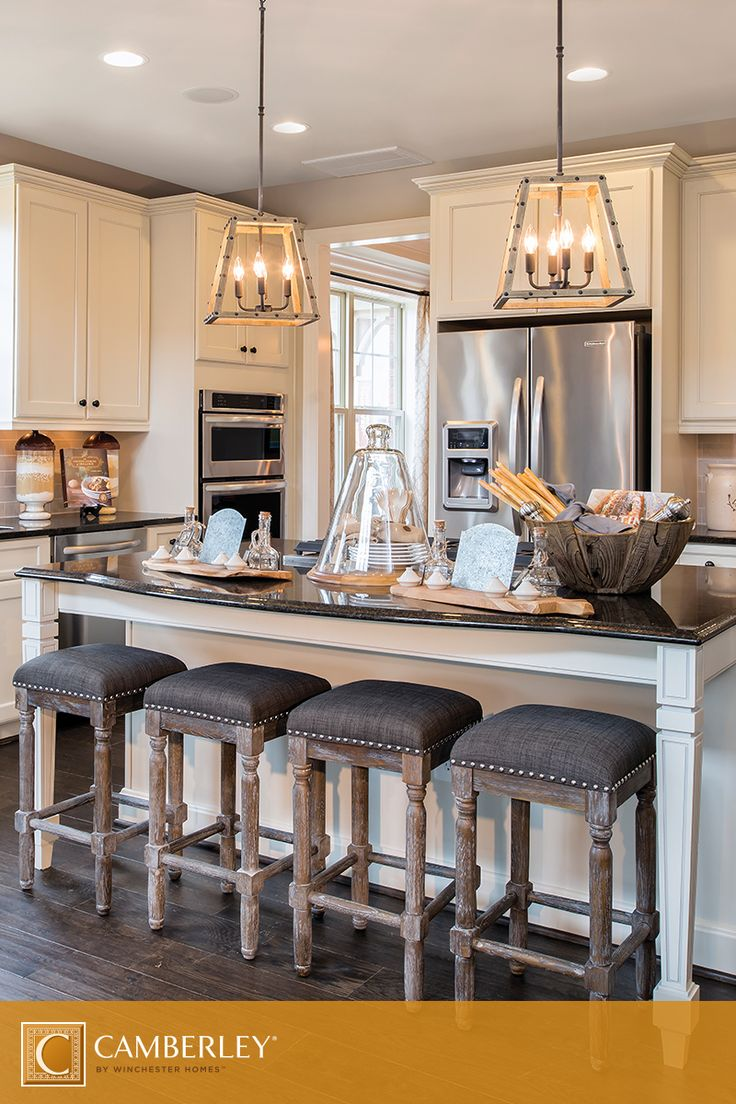 Rustic chandeliers, perfectly hung above the Landon's kitchen island, illuminate delectable dishes at dinner or when you're entertaining house guests. But the suspended lighting and black countertop also set the stage for everyday kitchen-themed decor. #DreamKitchen #InteriorDesign