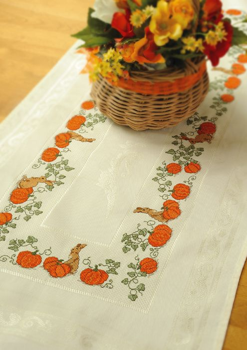 """""""In The Pumpkin Patch"""" Cross-stitch Table runner. Charming pumpkins and bunnies are stitched on a table runner base that boasts an elegant swirled border."""