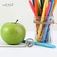 """TEACHER LOCKET """"A teacher takes a hand, opens a mind and touches a heart."""" Show your appreciation for a special teacher in your child's life with this gorgeous locket featuring a Large Silver Locket with Crystals, a colorful Artist Palette Charm, a delicious Apple Charm and a bright, yellow School Bus Charm."""