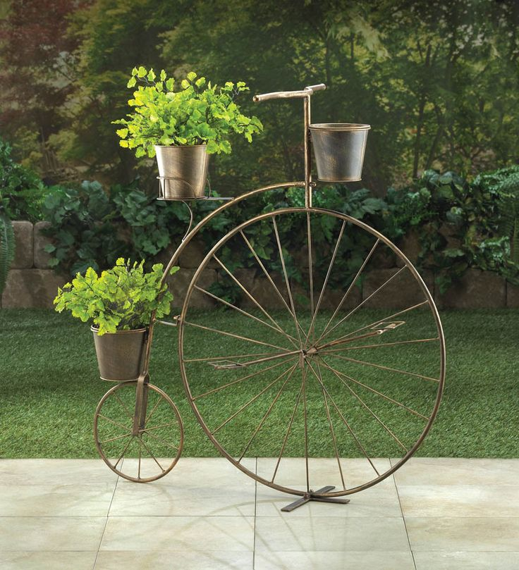 """Vintage charm is in bloom! This adorable planter's frame looks like a high-wheel bicycle from bygone days, with one large wheel in the front and a smaller wheel in back. Attached are three pails that are ready to hold your blooming plants. This lovely accessory will look great on your patio or in your favorite room.  Item weight: 5.4 lbs. 32"""" x 10"""" x 33¾"""" high. Iron. Plants not included.  Some Assembly Required.     Check out our Etsy shop!"""