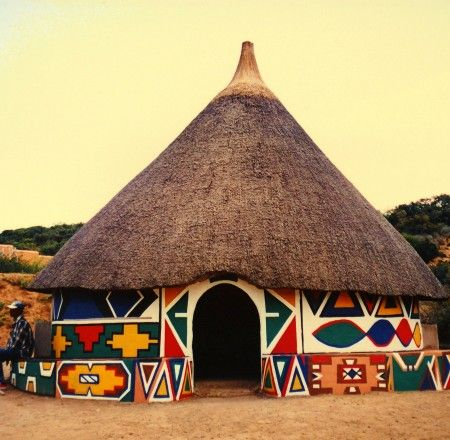 A beautiful colorful traditional ethnic African round hut of the Ndbele tribe in a village in South Africa in the peaceful evening sun