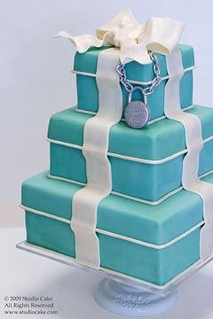 Three tier, square Tiffany Blue wedding cake. Looks just like a present cake or gift box cake. Beautifully decorated with a handmade silver fondant Tiffany's bracelet and white fondant ribbon and bow wedding cake topper.