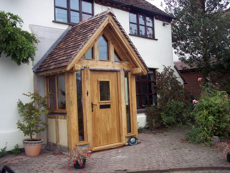 Oak porch with glass surrounds with red tile pitched roof.