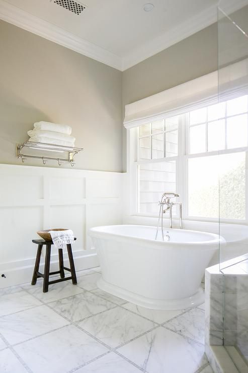 Beautiful transitional bathroom is fitted with a roll top freestanding bathtub paired with a polished nickel floor mount faucet fixed to white marble grid floor tiles accented with gray mosaic border tiles.