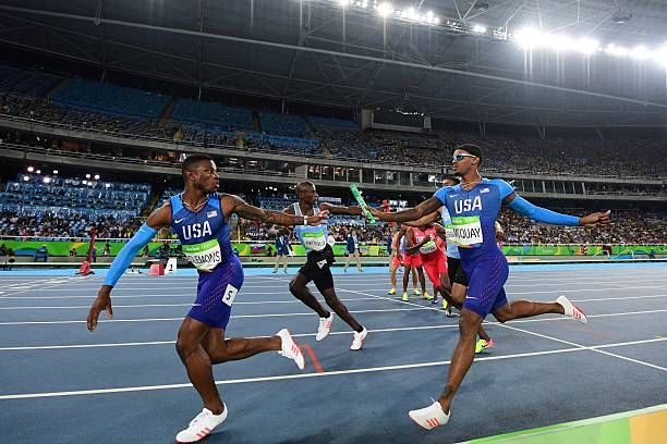 TOPSHOT - USA's Kyle Clemons (L) grabs the baton from USA's Tony McQuay as they compete in the Men's 4x400m Relay Round 1 during the athletics event at the Rio 2016 Olympic Games at the Olympic Stadium in Rio de Janeiro on August 19, 2016. / AFP / FRANCK