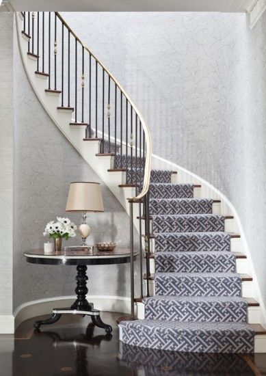 Gorgeous stairway by Markham Roberts. Textural gray wallpaper, grey graphic key runner contrasts it's sharp edges with the graceful swoop on the staircase, and don't miss the dark inlaid floors.