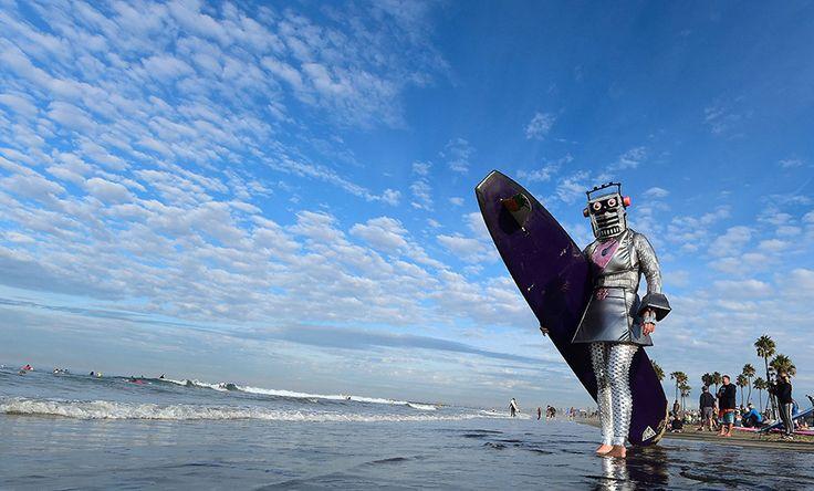 Ένας σέρφερ μεταμφιεσμένος  με στολή ρομπότ για το Halloween ετοιμάζεται να ανέβει με τη σανίδα του στα κύματα της παραλίας Νίουπορτ στη Καλιφόρνια.