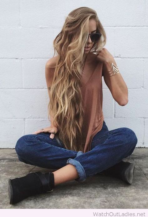 Black boots, blue jeans, nude top and very long hair