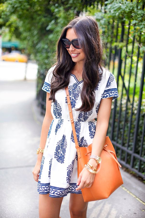 Opt for a Mediterranean-inspired print for your next summer sundress. Stay on-trend by accessorizing with a cognac bucket bag.
