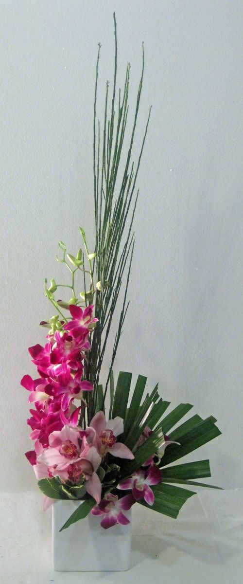Modenr Centerpiece Idea- Cymbidium and Dendrobium Orchids with Palms, Reeds and other Greens in White Container