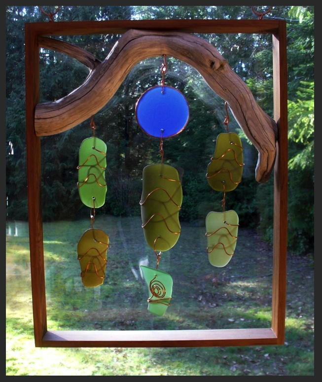 The frame measures 20 X 15 inches. It is cedar that has been treated with an exception eco-friendly tung nut oil finish. The glass is artist-made beach glass, which is smooth with a mat finish. The glass is wrapped in copper. There are handcrafted copper hooks for hanging.  CoastChimes, etsy.com, Tim Kline, Vancouver, BC