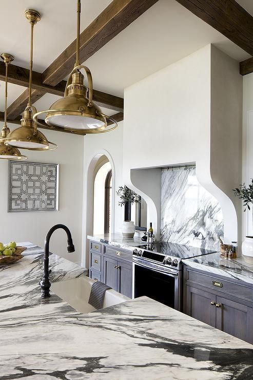 Beautiful kitchen features gray wash cabinets paired with dark gray and white marble countertops.
