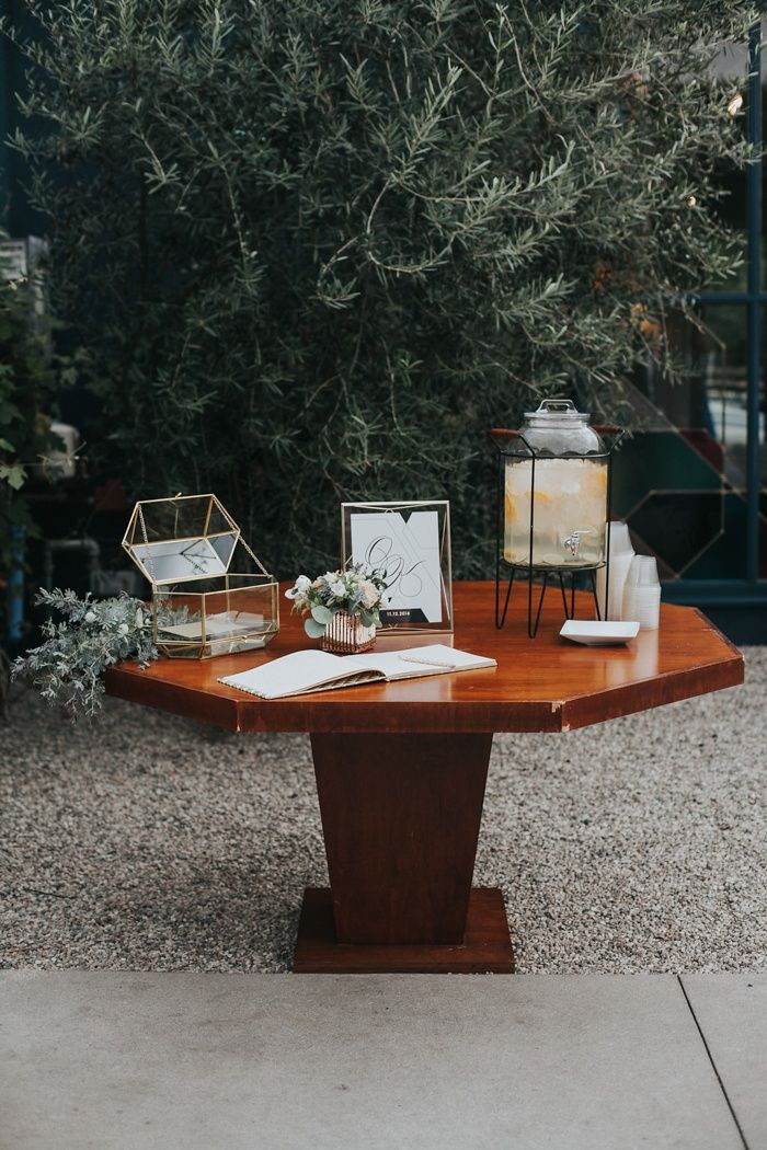 Modern welcome and guest book table with geometric gold card box and water station | Image by Rachel McCauley Photography
