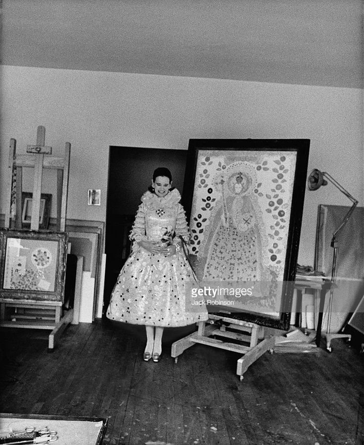 Gloria Vanderbilt (aka Mrs. Wyatt Emory Cooper) standing in front of one of her collages, and wearing a dress designed especially for her by Adolfo, based on one of her paintings: deep neck ruff of silver lace, bouffant skirt and bodice decorated all over with metallic paillettes, faux flowers, silver lace, and ribbons.