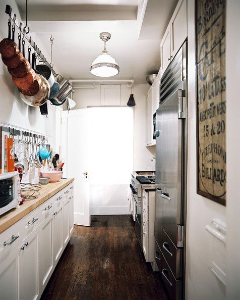 High and Dry In a slim kitchen, use the height of the room to your advantage: clunky pots and pans look beautiful cascading from the ceiling and free up coveted counter space.