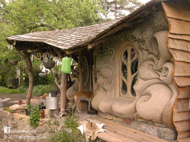 little house with sculpted cob walls looks out over the banks of a small stream in Somerset, England