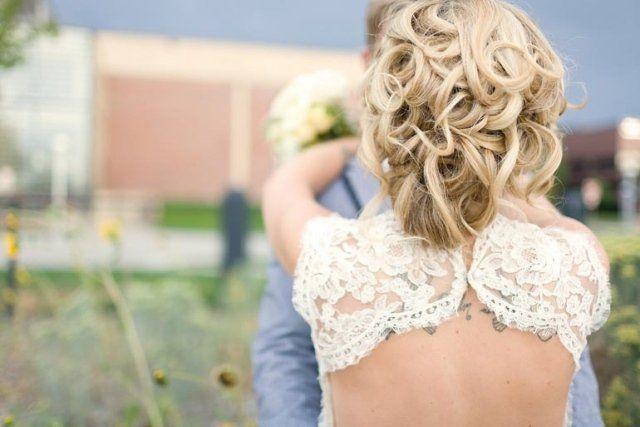 coiffure mariée cheveux bouclés tatouage femme sur le dos