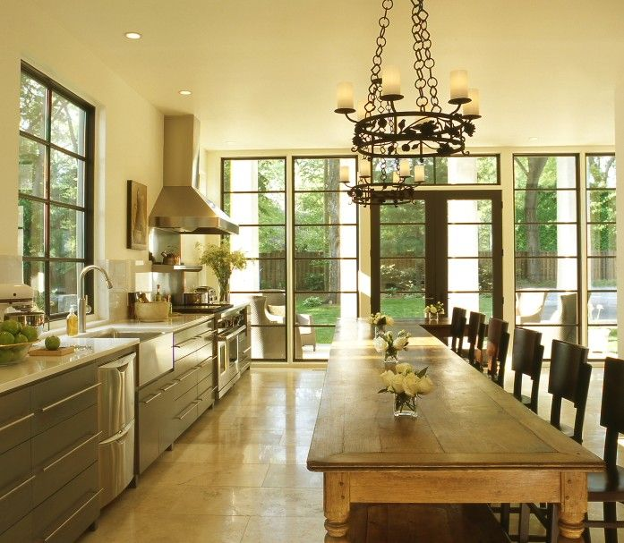 kitchens - gray green modern kitchen cabinets marble countertops stainless steel apron sink endless kitchen island dining table iron candelabras French doors travertine tiles floor