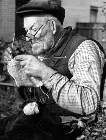 England, 1940's. An old man knitting to help the war effort during World War2.
