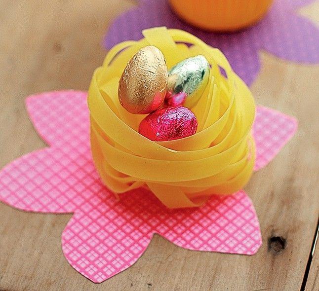 Para os ovinhos menores, faça uma brincadeira: coloque-os em ninhos feitos de macarrão ou forminhas de cupcakes. Para a base, corte um papel estampado em forma de flor  (Feliz Páscoa   Happy Easter)
