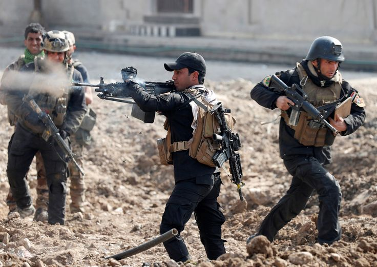 Nineveh governorate. Mosul. March 1, 2017. An Iraqi special forces soldier fires as other soldiers runs across a street during a battle. Photograph: Goran Tomasevic/Reuters