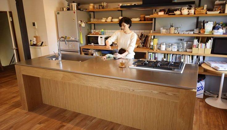 ステンレスバイブレーションとオークを使ったアイランドキッチン。キッチン:オーク板目突板練り付け、水栓器具:TOTO TKWC、ガスコンロ:HARMAN +do、レンジフード:ARIAFINAセンターフェデリカブラック、