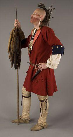 modèle portant manteau rouge, des jambières en cuir et la tenue de la lance