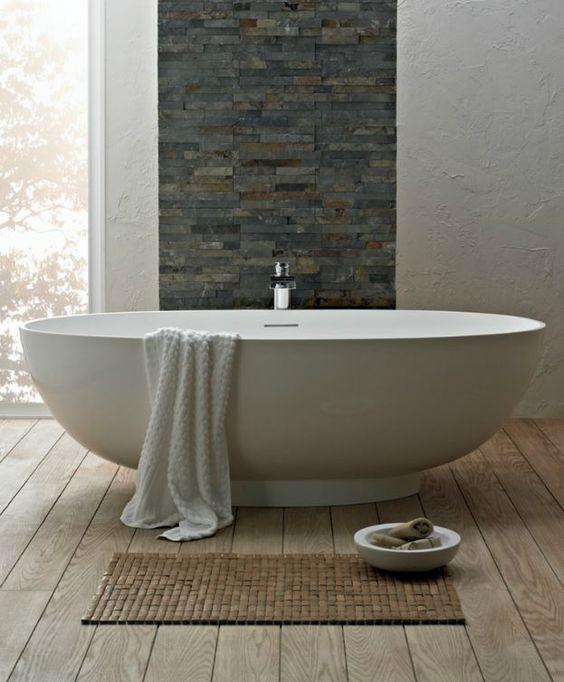 Vrijstaand bad met natuursteen muur en houten vloer