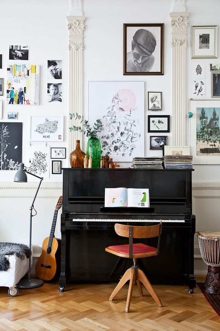 Living space with herringbone wood floors and a piano