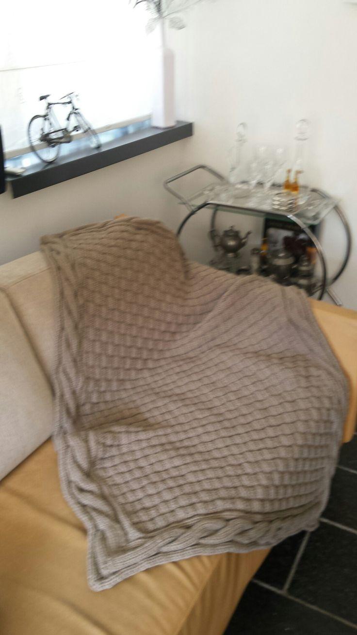 Gebreide deken. De rand met kabels is aan een stuk  gebreid.