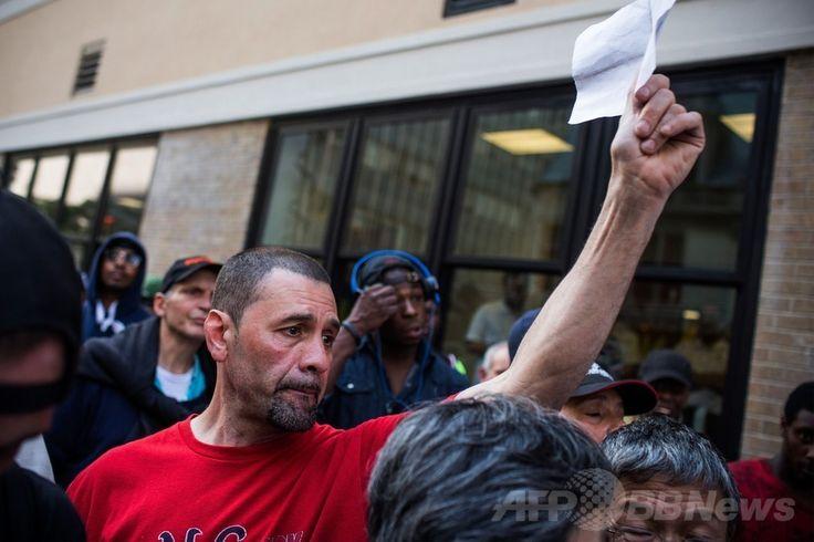 米ニューヨーク(New York)の「ニューヨーク市救助ミッション(New York City Rescue Mission)」外で、中国人富豪の陳光標(Chen Guangbiao)氏が約束した300ドルのプレゼントを求める男性(2014年6月25日撮影)。(c)AFP/Getty Images/Andrew Burton ▼26Jun2014AFP|米NYホームレス、中国人富豪の招待ランチに「ペテンだ」と激怒 http://www.afpbb.com/articles/-/3018861