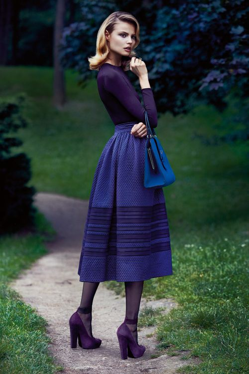purple-blues, fitted long-sleeved top with a full skirt, a sleek purse, and great hair