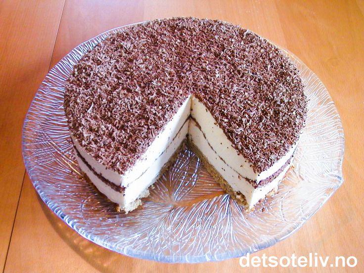 """Her har du en festkake som slår """"knock-out"""" på de fleste andre! """"Dronning Maud pudding"""" er en nydelig festdessert som ble spesialkomponert en gang Dronning Maud besøkte Haugesund for mange år siden. Desserten består av flere lag med luftig eggefromasj og kokesjokolade, og serveres ofte til jul, brylluper og konfirmasjoner - gjerne med kransekake som tilbehør. """"Dronning Maud kake"""" er en fromasjkake basert på de samme ingrediensene som den berømte desserten, i tillegg til at den inneholder en…"""