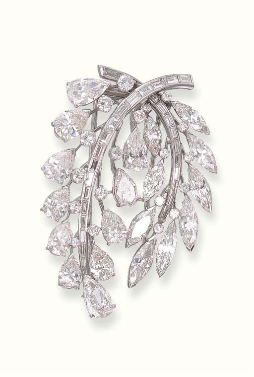 AN ATTRACTIVE DIAMOND CLIP BROOCH. Designed as pear-shaped and marquise-cut diamond twin leaves with circular-cut diamond detail to the baguette-cut diamond stems.