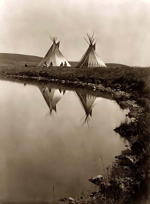 Two tepees reflected in water of pond. Tipi, water, reflections, silence, vintage, photo, history.