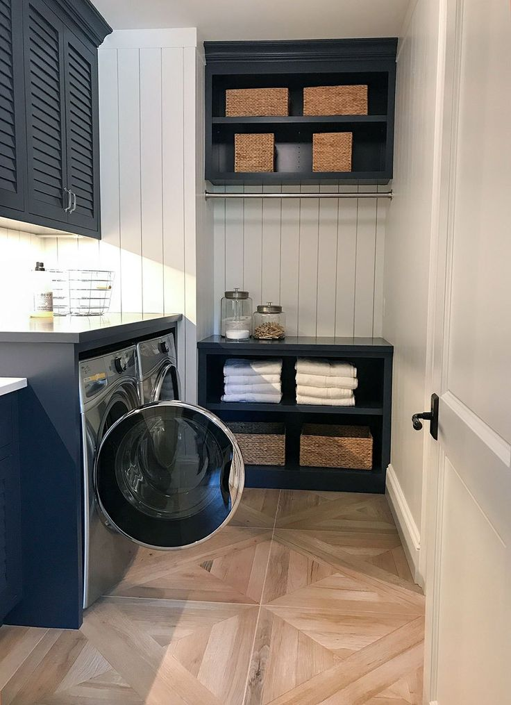Second floor laundry room with light natural floors, navy cabinets, white shiplap walls