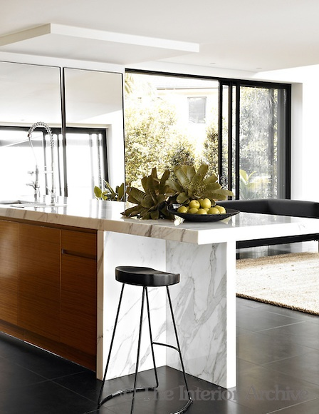 A Calcutta marble kitchen island separates the living and dining areas in the open plan space