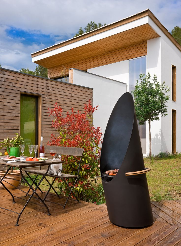 Diagofocus by Focus. It's both a barbecue grill and a outdoor fireplace.  Made of black steel. Can be wheeled to turn its back to the wind to help protect hosts and guests from smoke.