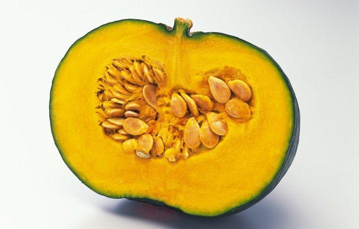 На фотографии изображена тыква в разрезе, видная желтая мякоть и косточки