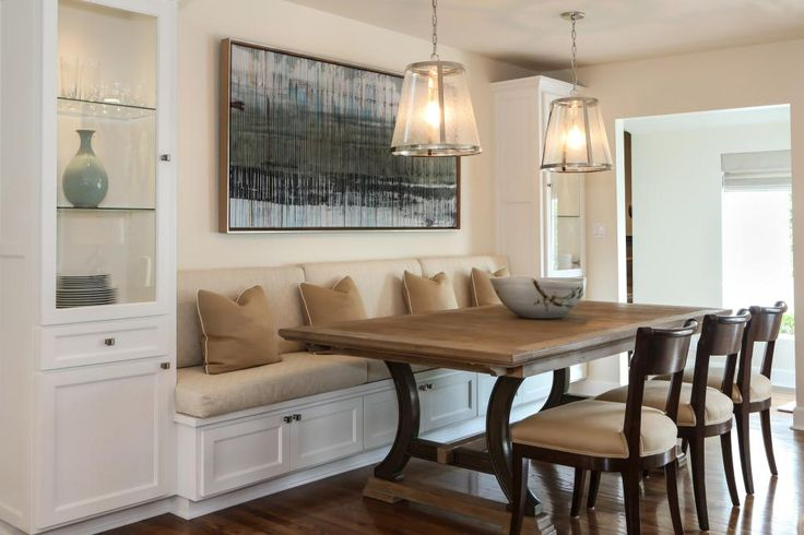 A built-in banquette is flanked by tall glass cabinets for storing dishes and glassware, while a trio of chairs provides more seating on the other side of the table. A large contemporary art piece brings in a splash of color and rounds out the space.