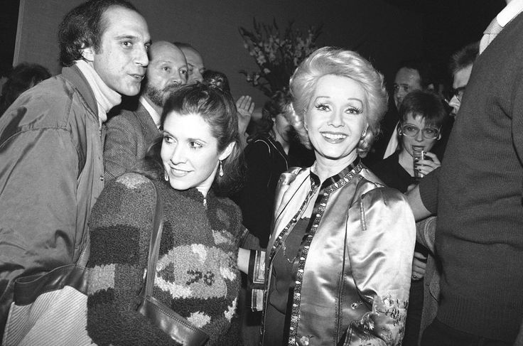 """Actress Debbie Reynolds, right, and daughter actress Carrie Fisher have smiles for the crowd of well wishers at a party in New York, Feb. 17, 1983 marking Miss Reynolds' return to Broadway. Miss Reynolds steps into """"Woman of the Year"""" which previously starred Lauren Bacall and Raquel Welch. (AP Photo/Nancy Kaye)"""