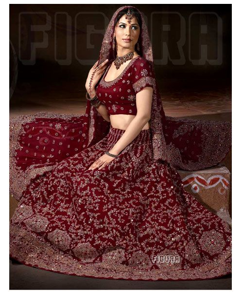 Bridal Traditional Maroon color! Lehenga is intricately decorated with zardosi and zari embroidered floral patterns. Kundans and sequins are embedded all over, lending it a glittery look! Choli is embellished with kundans, sequins and zardosi worked motifs. Dupatta is in maroon with sequins, kundans, zardosi and zari work in floral motifs. Pure hand work.
