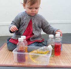 Bébé joue avec bouteilles colorées Montessori
