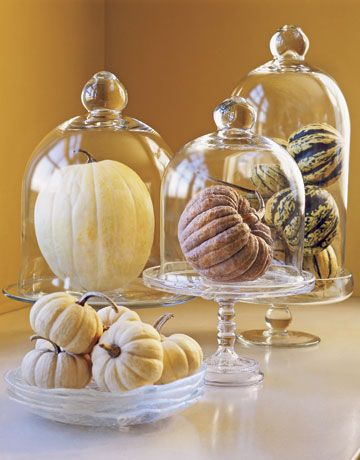 Quick fall centerpiece: Corral small gourds under glass cloches and on small cake stands.